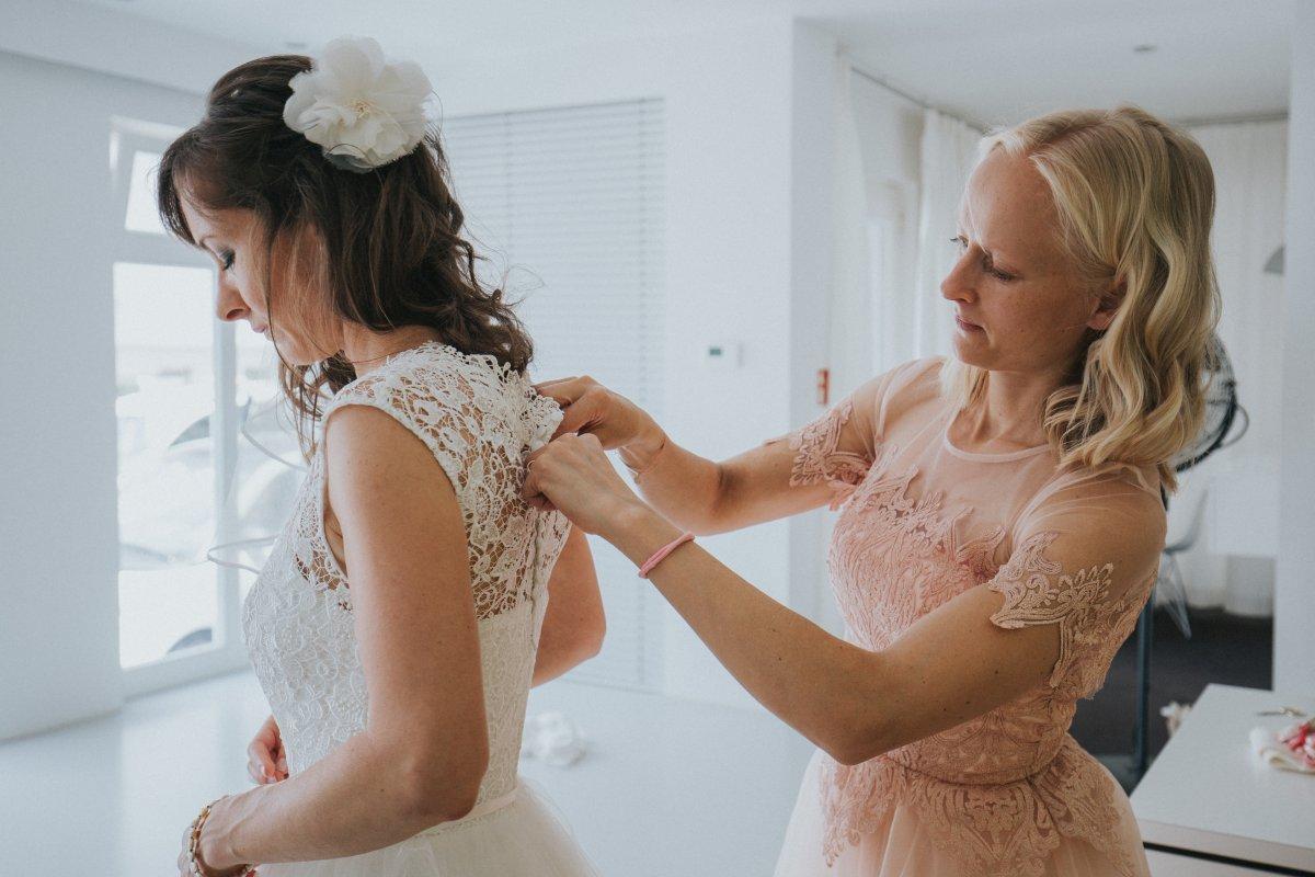 Trauzeugin hilft der Braut beim Anziehen