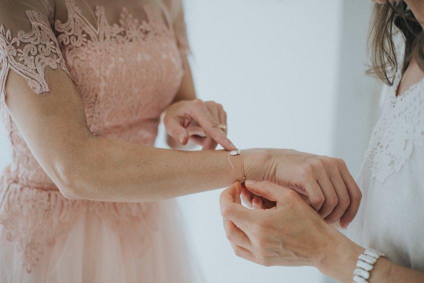 Braut zieht der Trauzeugin ein Armband an