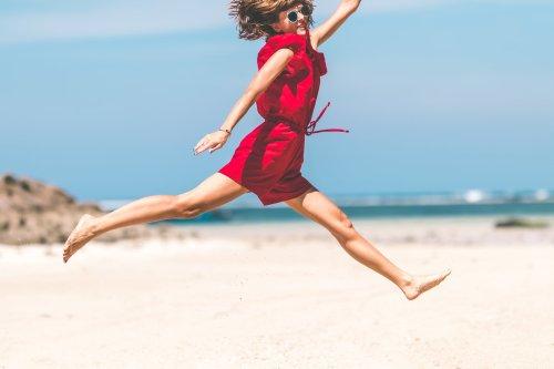 Frau springt am Meer in die Luft