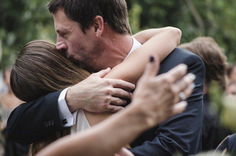 Vater umarmt die Braut